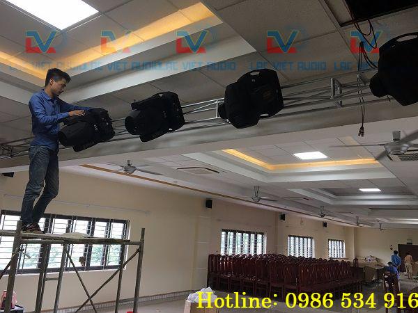 Nhân viên kỹ thuật Lạc Việt Audio treo đèn Beam 230 lên giá đỡ sân khấu